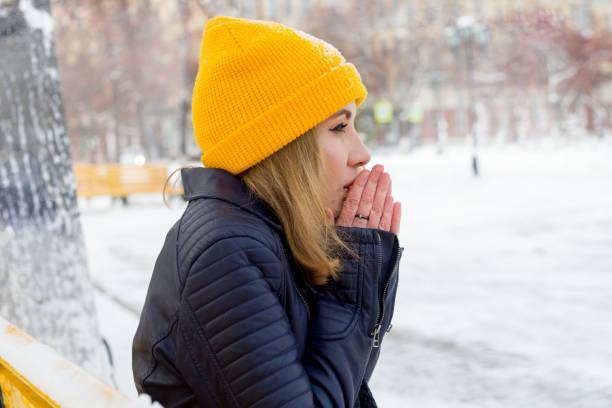 hermosa joven calienta sus manos en la calle - frío fotografías e imágenes de stock
