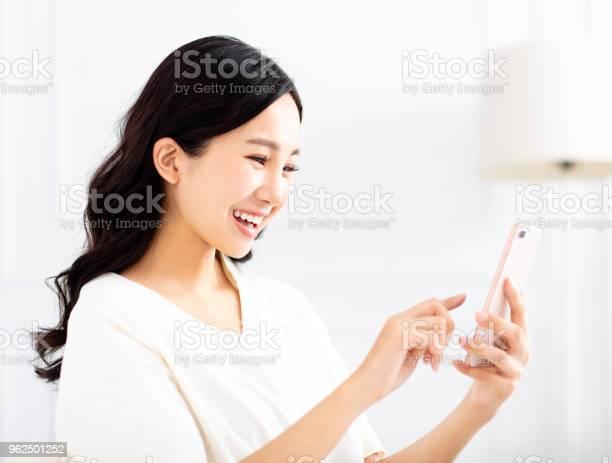 Foto de Mulher Jovem E Bonita Assistindo O Telefone Móvel e mais fotos de stock de Adulto