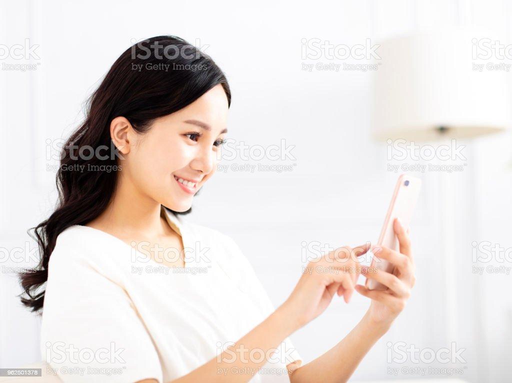 mulher jovem e bonita assistindo o telefone móvel - Foto de stock de Adulto royalty-free