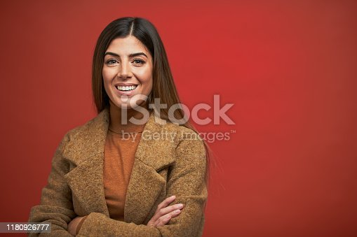Studio headshot on white background. Spanish model. Beautiful young woman wearing a coat and looking at the camera.