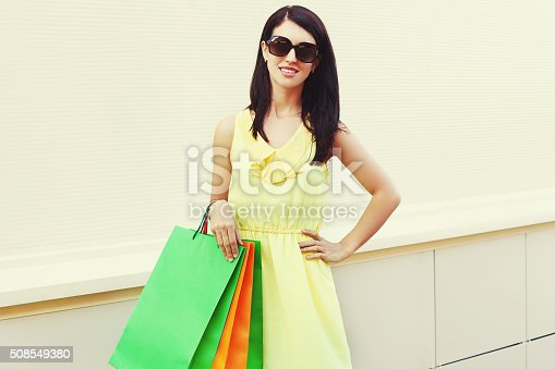 istock Beautiful young woman wearing a yellow dress with shopping bags 508549380