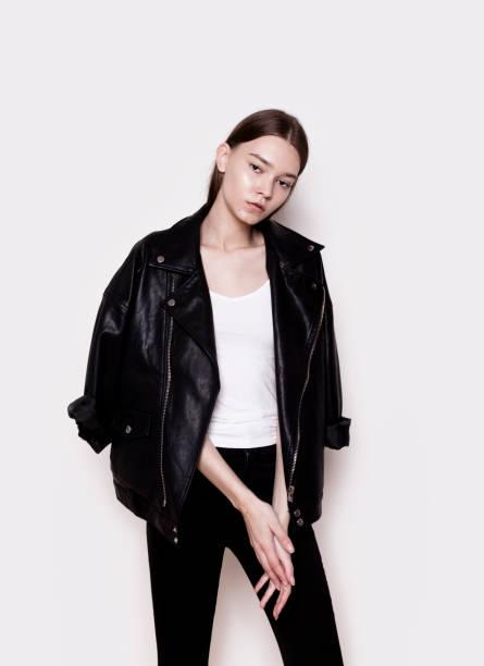 schöne junge frau trägt schwarze lederjacke und weiss top studioportrait - damenjacken stock-fotos und bilder