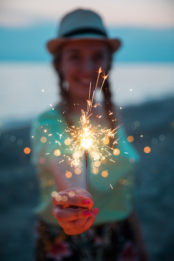 beautiful young woman wearing braids and straw hat at the sunset beach. she is blurred with focus in the sparkler. Celebration time and happiness concept