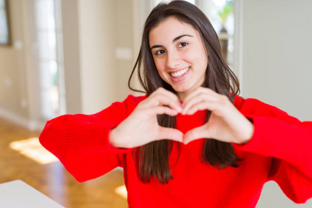 Beautiful young woman wearing casual red sweater smiling in love showing heart symbol and shape with hands. Romantic concept. Beautiful young woman wearing casual red sweater smiling in love showing heart symbol and shape with hands. Romantic concept. red shirt stock pictures, royalty-free photos & images