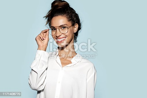 Portrait of gorgeous lady touching spectacles with hands and looking at camera with gladness. Beauty and fashion concept. Isolated on blue background. Copy space in right side