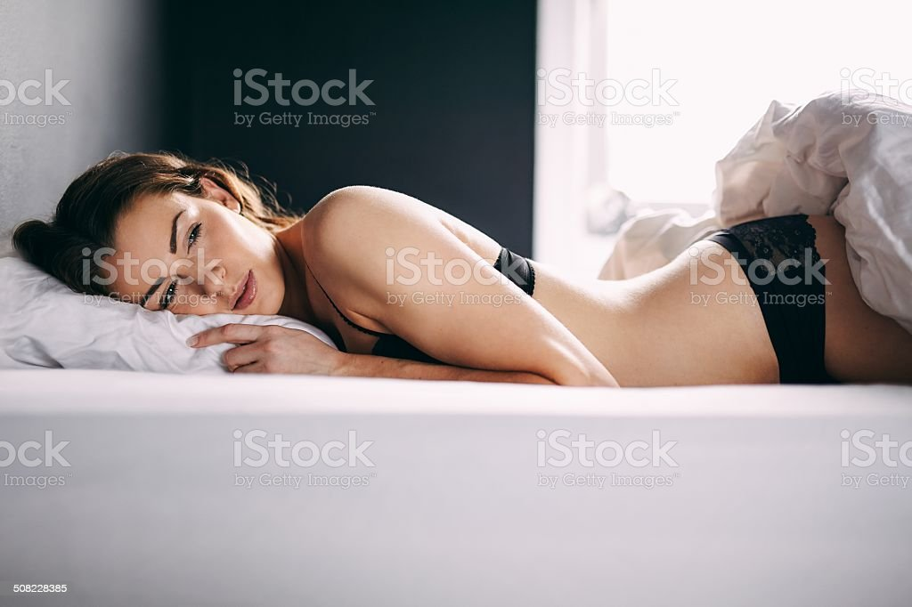 Beautiful young woman wearing lingerie lying in her bed stock photo