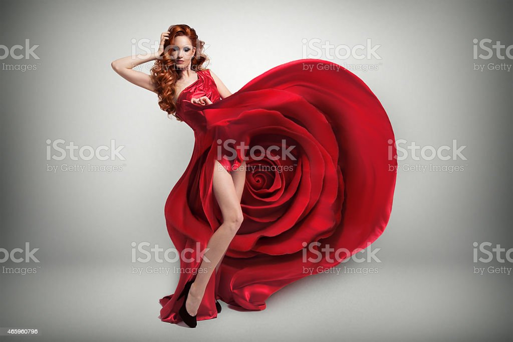 Beautiful young woman wearing red rose dress. stock photo