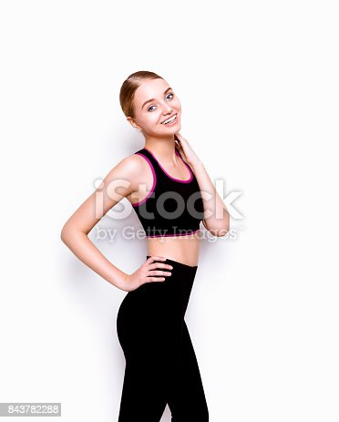 Beautiful young woman with perfect body shape wearing sport clothes gray top and black pants looking fresh happy and healthy Fashion model studio portrait on white background