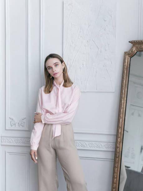Beautiful young woman wearing vintage pink blouse and beige pants in Parisian apartment Luxury lifestyle Beautiful young woman wearing vintage clothing pink blouse beige wide leg pants She is Parisian apartment standing next to antique mirror Looks gorgeous confident with fresh natural make-up Amazing interiour  Sophisticated life blouse stock pictures, royalty-free photos & images