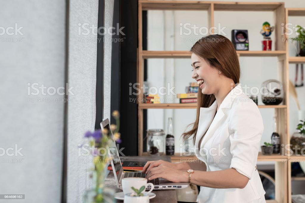 Beautiful young woman who is an Asian businessman smiling happy working with a laptop in a coffee shop Cafe. royalty-free stock photo