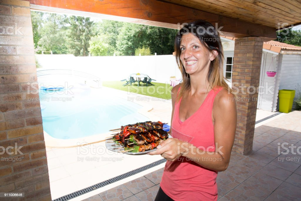 beautiful young woman will serve barbecue skewers and sausages stock photo