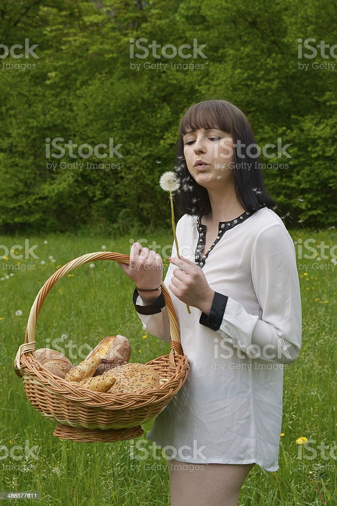 Beautiful young woman with a basket full of baked bread stock photo