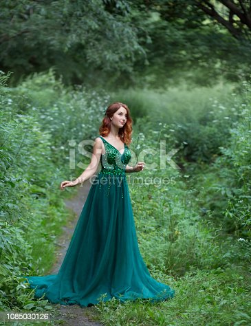 745307a7b 1085032090istock Una mujer joven hermosa con un pelo rojo. vestido con una  larga pluma.