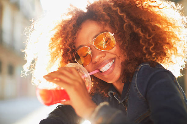 beautiful young woman with afro, summer time. - drinking juice stock photos and pictures