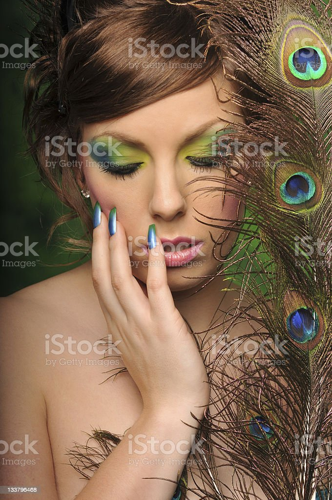 Beautiful young woman with artistic makeup and peacock feathers royalty-free stock photo