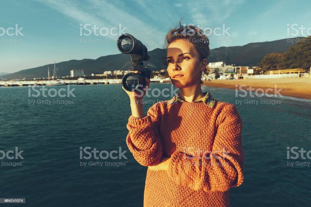 Beautiful Young Woman With Binoculars In Hand Standing By The Sea And Enjoying View Of Nature royalty-free stock photo