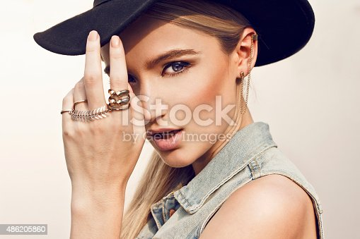 Close up of beautiful young  blonde woman with black hat. Wearing denim vest. Her hair is tied to ponytail.