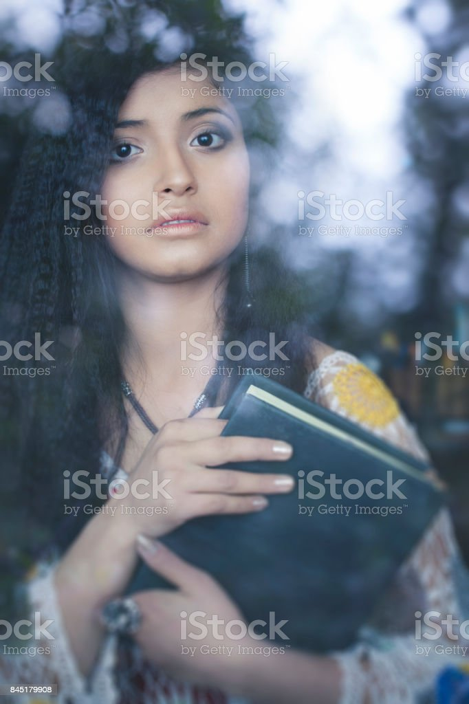 Beautiful young woman with book behind glass window. stock photo