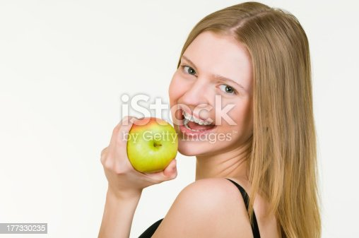 istock Beautiful Young woman with brackets eating apple 177330235
