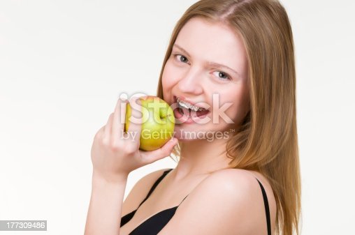 istock Beautiful young woman with brackets on teeth eating apple 177309486