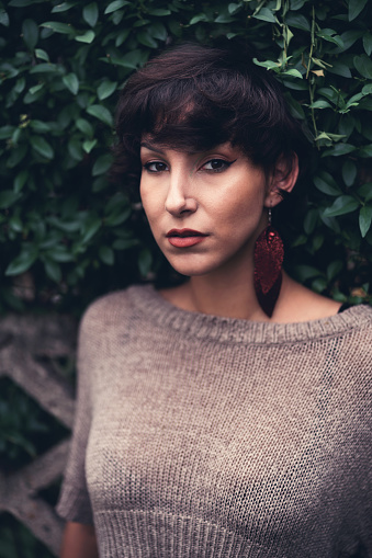 Beautiful, young, Caucasian woman with brown hair and brown eyes posing in front of the concrete fence in the nature.