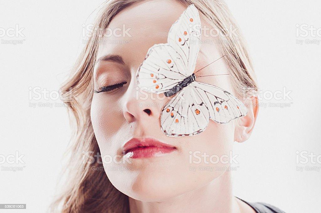 Bela jovem mulher com borboleta no rosto dela - foto de acervo
