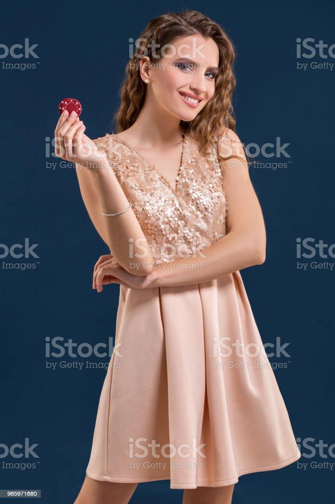 Mooie jonge vrouw met casino chips op donker blauwe achtergrond - Royalty-free Alleen volwassenen Stockfoto