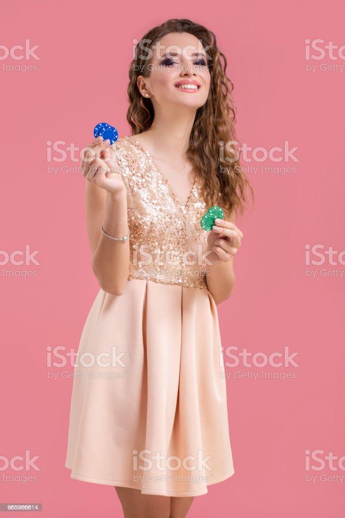 Schöne junge Frau mit Casino-Chips auf rosa Hintergrund - Lizenzfrei Archivmaterial Stock-Foto