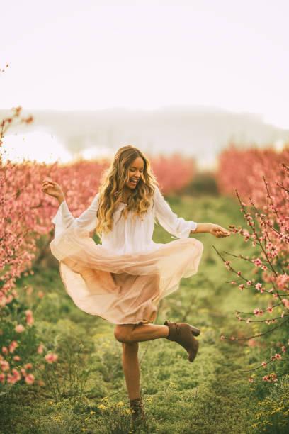 schöne junge frau mit kirschblüte im frühling - damen rock lang stock-fotos und bilder
