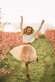 Very happy carefree woman standing among cherry threes with flower blossoms at spring. She is jumping, dancing, enjoying life
