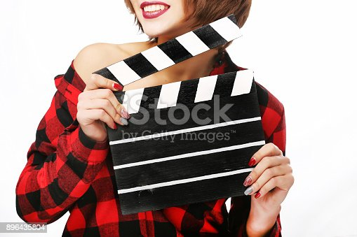 istock Beautiful young woman with cinema clapper posing in studio. Movie concept. Isolated. 896435804