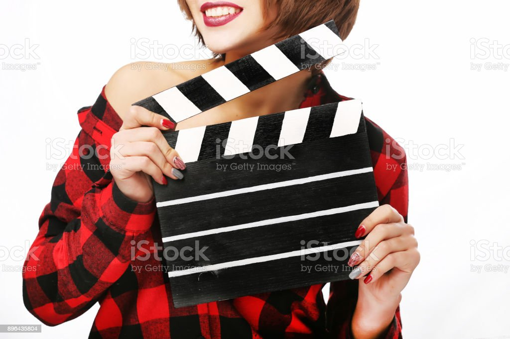 Beautiful young woman with cinema clapper posing in studio. Movie concept. Isolated. stock photo