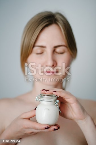 532331272 istock photo A beautiful young woman with clean fresh skin holds a white jar with a face cream isolated on grey background. The concept of the use of cosmetics for the body and moisture. Facial care. 1161298354