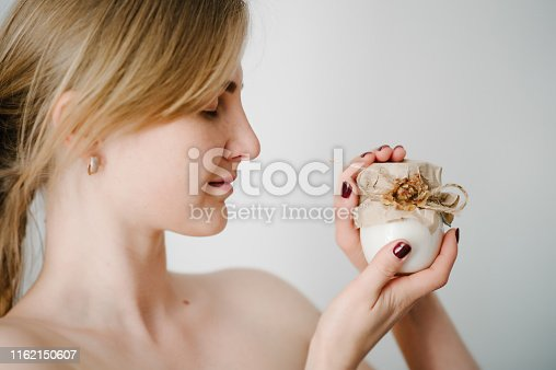 532331272 istock photo A beautiful young woman with clean fresh skin holds a white jar with a face cream isolated on grey background. The concept of the use bottles of natural cosmetics for the body and moisture. Facial care. 1162150607