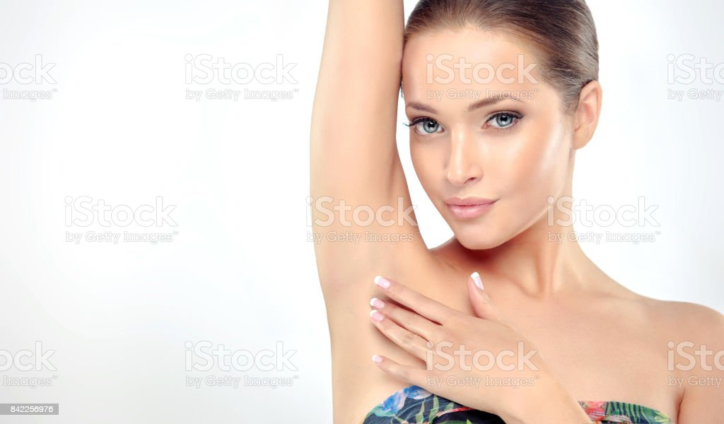 Beautiful young woman with clean, fresh skin is holding her arms up and showing underarms. stock photo
