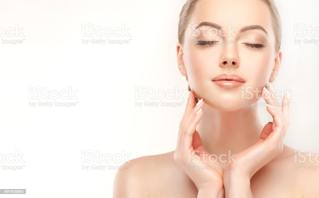 Beautiful young woman with clean, fresh skin is touching own face. Cosmetology. stock photo
