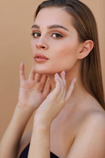 Beautiful Young Woman with Clean Fresh Skin touching own face. Facial treatment stock photo