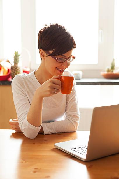 schöne junge frau mit kaffee und mit laptop in der küche - marko skrbic stock-fotos und bilder