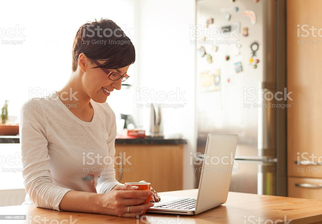 Beautiful young woman with coffee using laptop in the kitchen stock photo