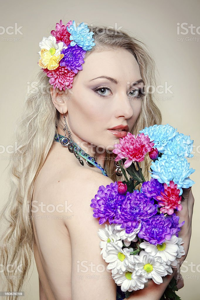 Beautiful young woman with colorful flowers in hair royalty-free stock photo