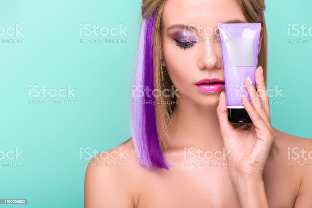 beautiful young woman with colorful hair holding hair tonic tube...