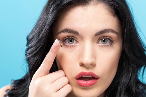schöne junge frau mit kontaktlinsen - blaue kontaktlinsen stock-fotos und bilder