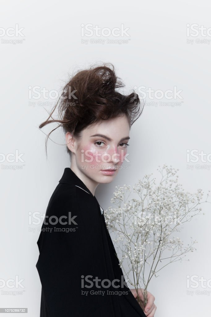 76ef4d612 Beautiful young woman with creative make-up and hairstyle wearing stylish  clothes holding pretty white