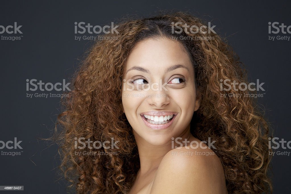 Beautiful young woman with curly hair laughing and looking away royalty-free stock photo