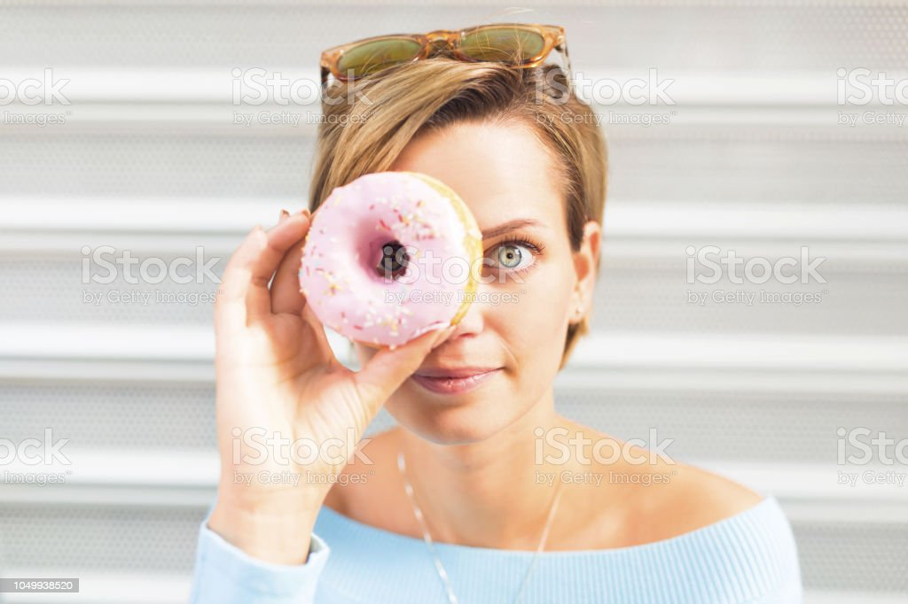 Beautiful young woman with donut stock photo