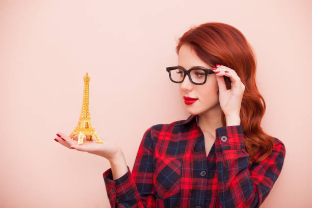 beautiful young woman with eiffel tower toy on the wonderful pink background stock photo
