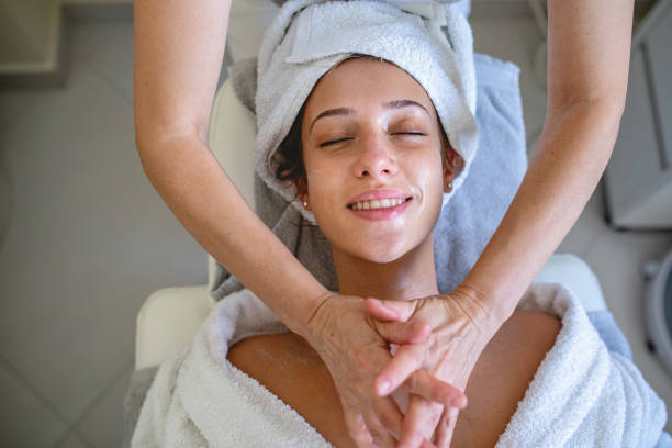 beautiful young woman with facial mask on a massage table - chemical peel stock pictures, royalty-free photos & images