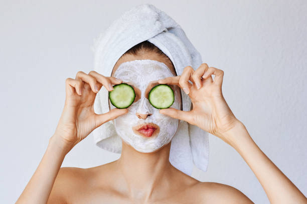 Beautiful young woman with facial mask on her face holding slices of fresh cucumber stock photo