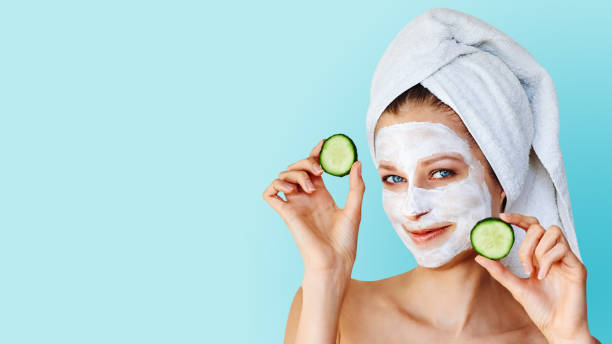Beautiful young woman with facial mask on her face holding slices of cucumber stock photo