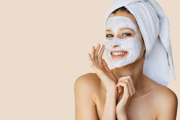 Beautiful young woman with facial mask on her face stock photo